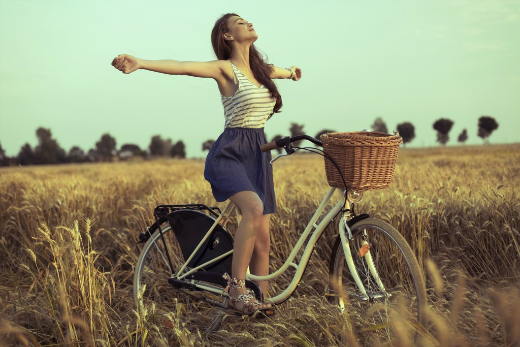 Free woman enjoying freedom on bike on wheat field at sunset